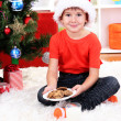 Royalty-Free Stock Photo: Little boy in Santa hat with milk and cookies for Santa Claus