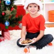 Little boy in Santa hat with milk and cookies for Santa Claus - Stock Photo
