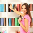 Female student selecting book from library shelf — Stok fotoğraf