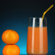 Delicious tangerine juice in glass and mandarins next to it on dark blue background — Stock Photo #17407039