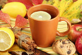 Cup of hot tea and autumn leaves, on wooden table — Stock Photo