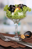 Snack of mussels and lemon on vase on wooden table on room background — Stock Photo