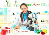 Young scientist looking into microscope in laboratory — Foto de Stock