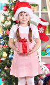 Happy little girl with Christmas toys in festively decorated room — Stock Photo