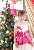 Beautiful little girl in holiday dress in festively decorated room — Stock Photo