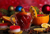 Fragrant mulled wine in glass with spices and oranges around on wooden table on red background — Stock Photo