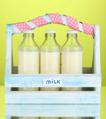 Milk in bottles in wooden box on green background — Stock Photo