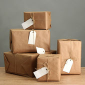 Cajas de paquetes con papel kraft, en mesa de madera sobre fondo gris — Foto de Stock