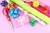 Rollen van kerstmis inpakpapier met linten, bogen op kleur achtergrond — Stockfoto