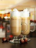 Geurende koffie latte in glazen bekers met noten, op tafel in café — Stockfoto