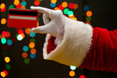 Santa Claus hand holding credit card, on garland background — Stock fotografie