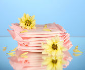 Panty liners in individual packing and yellow flowers on blue background close-up — Stok fotoğraf