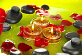 Spa stones with rose petals and candles in water on plate — Foto Stock