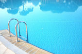 Hotel swimming pool with sunny reflections — Stock Photo