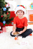 Little boy in Santa hat with milk and cookies for Santa Claus — Stockfoto