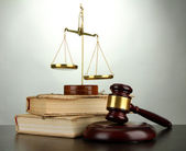Golden scales of justice, gavel and books on grey background — Stockfoto