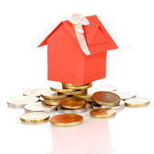 Small house standing on heap of coins — Stock Photo
