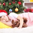 The little girl fell asleep with gift in their hands in festively decorated room - Stock Photo