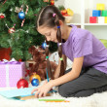 Little girl writing letter to Santa near christmas tree — Stock Photo #17593681