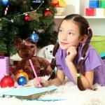 Little girl writing letter to Santa near christmas tree — Stock Photo #17593683