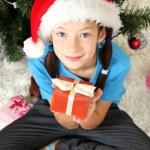 Little girl holding gift box near christmas tree — Stock Photo #17593689
