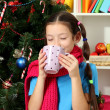 Little girl with pink scarf and cup of hot drink sitting near christmas tree — Stock Photo #17593691