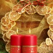 Two candles and christmas decorations, on golden background - Стоковая фотография