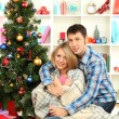 Young happy couple near a Christmas tree at home — Stock Photo