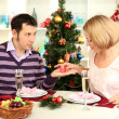 Young happy couple with presents sitting at table near Christmas tree — Stock Photo #17593817
