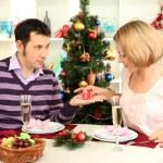 jonge gelukkige paar met presenteert zitten aan tafel in de buurt van de kerstboom — Stockfoto