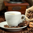 Cup of coffee, grinder, turk and coffee beans on brown background — Stock Photo #17594067