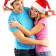 Stockfoto: Loving couple in Santa hats isolated on white