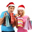 Young couple in Santa hats shopping and holding many shopping bags isolated on white — Stock Photo #17594249
