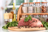 A large piece of pork marinated with herbs, spices and cooking oil on board on white table on window background — Stock Photo