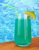 Glass of blue cocktail on blue background — Stock Photo
