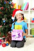 Little girl holding gift boxes near christmas tree — Stock Photo