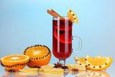 在玻璃与香料和周围在蓝色背景上的橘子香芬芳的美酒 — 图库照片