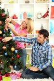 Young happy couple decorates Christmas tree at home — Stock Photo