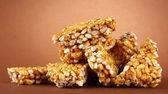 Tasty sweets (kozinaki), on brown background — Stock Photo