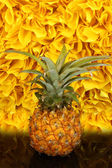 Ripe pineapple on black table on yellow decorative background — Stock Photo