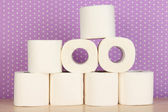 Rolls of toilet paper on purple with dots background — 图库照片