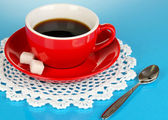 A red cup of strong coffee on blue background — Stock Photo