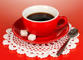 A red cup of strong coffee on red background — Stock Photo