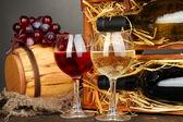 木箱与葡萄酒瓶、 桶、 酒杯和灰色的背景上的木桌上的葡萄 — 图库照片