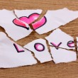 Torn paper with words Love close-up on wooden table - Stock Photo