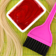Royalty-Free Stock Photo: Hair dye in bowl and brush for hair coloring on green bamboo mat, close-up