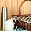 Metal thermos with cups, plates and basket on grass on wooden background — Stock Photo #17619417
