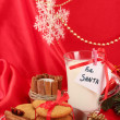 Cookies for Santa: Conceptual image of ginger cookies, milk and christmas decoration on red background — Stock Photo #17619695