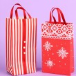 Christmas paper bags for gifts on purple background - 图库照片
