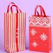 Christmas paper bags for gifts on purple background - Lizenzfreies Foto